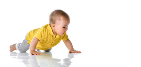 Adorable positive little baby in a yellow polo and gray pants and barefoot trying to crawl on the floor smiling and looking to the side on a white background. Happy childhood concept