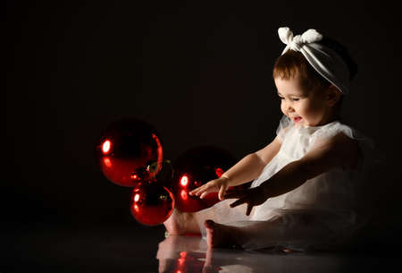 Funny little girl in a white dress dressed as snowflakes sits on the floor in the darkness and plays with Christmas red balls.