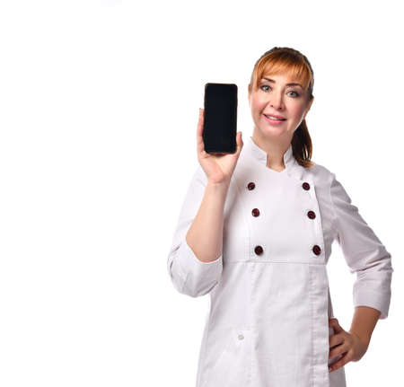 female doctor in medical gown looking forward showing to smartphone screen for mockup. Close up isolated on white, copy space. Nurse, ambulance, healthcare, technology