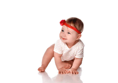 Pretty adorable crawling baby girl studio portrait. Female six month toddler child wearing body stretchie and red headband with positive facial emotion. Smiling newborn child. Innocence and babyhood