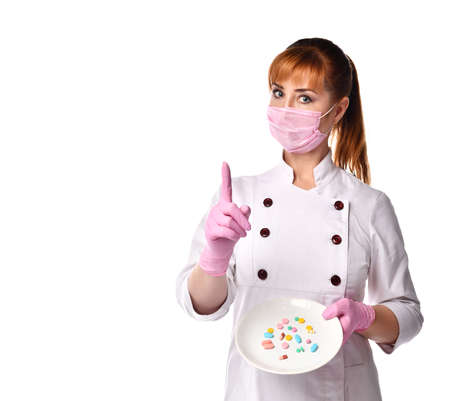 Confident female doctor in a medical mask holding a plate with assorted pills, pointing her index finger up. Waist up shot isolated on white, copy space. Medical assistance, healthcare, be careful