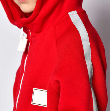 Closeup shot of warm red jumpsuit hood on boy model. Crop studio shot of trendy design sport wear for children. Detailed photo of costume for training and outdoor walk in autumn
