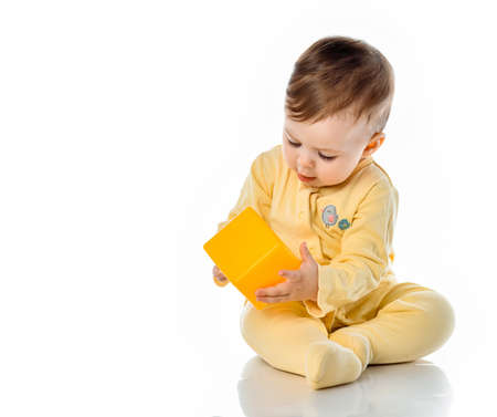 joyful happy kid play with yellow toy plastic cube sitting on the floor. Uses a toy as a teether