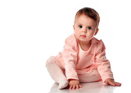 Cute baby girl sits on a white background. Adorable little kid looking at the camera. The studio shot a portrait of a sweet baby wearing a pink skirt, sweater and tights. Stockfoto