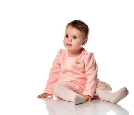 Baby girl sitting on studio floor isolated on white background. Adorable little child looking away. Studio shot portrait of sweet infant kid wearing pink skirt, sweater, tights. Children fashion style
