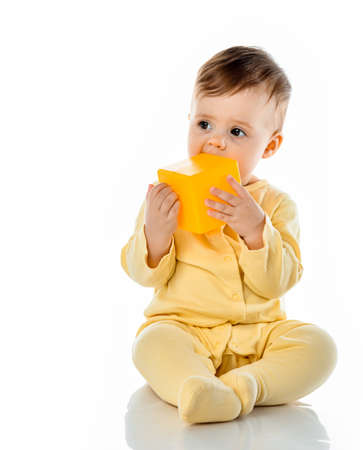 Little cute baby child gnawing toy chewing yellow block cube sitting on floor. Ecological hygienic healthy safe toy for toddler children. Studio full length portrait isolated on white copy space