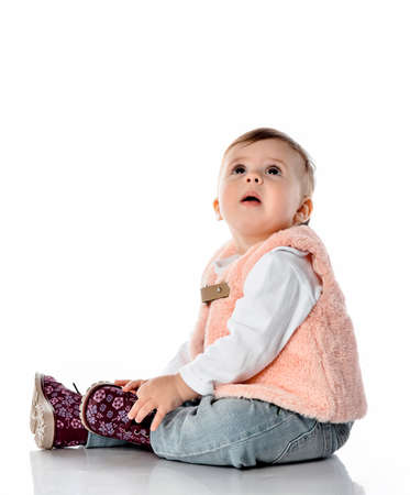 Amazed baby girl wearing warm winter or autumn trendy outfit clothes and colorful shoes sitting on white floor looking up studio shot on white copy space. Funny toddler child full length portrait Stockfoto