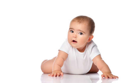 Portrait of a concerned baby girl with brown eyes on a white background. Child dressed in a white bodysuit crawls on all fours on the floor in the studio. Free space for text.
