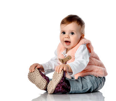 Joyful cute girl sitting on the floor touching new fashionable shoes on her feet in full length studio portrait on white copy space. Beautiful kids fashion outfit and fashion for autumn and winter Stockfoto