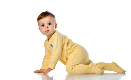 little cute baby girl in a yellow bodysuit tries to crawl on a white studio background.