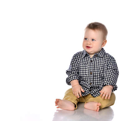 Portrait of a little one-year-old boy on a white background. The boy sits in a shirt and shorts with tears in his eyes. The boy is capricious because his toy was taken away. The concept of children's whims.