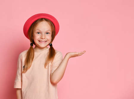 Funny blond child in a hat and a t-shirt. She smiles and acts as if holding something in the palm of her hand. Posing against a pink studio background. Childhood, emotions, advertising.