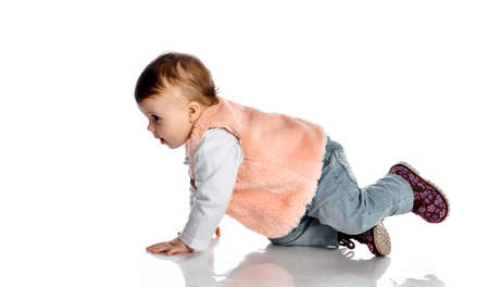 Portrait of a little girl in stylish clothes crawling to the side in jeans and pink fur vest Stockfoto