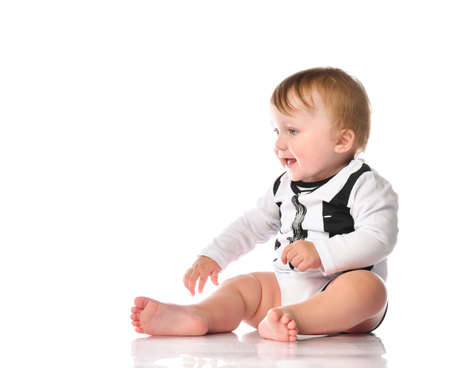 boy toddler portrait with blue eyes dressed in black and white bodysuit. The child is sitting barefoot and smiling happily on a white background with space for text. Foto de archivo