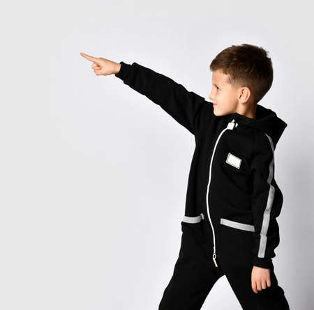 Handsome boy in black warm jumpsuit pointing finger forward to copy space looking aside. Side view crop studio shot on wall background. Junior fashion, casual outfit, trendy attire for children advert Stockfoto