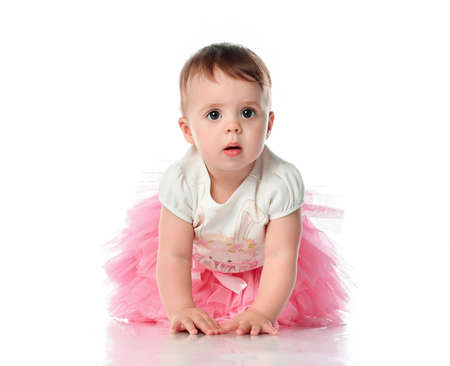 Image of sweet baby girl in a pink skirt on a white background