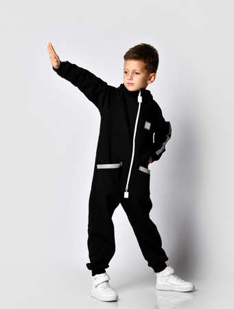 Handsome boy in black warm jumpsuit standing with raised hand palm over studio copy space looking aside. Junior fashion, casual outfit, trendy attire, sportive wear for children advertisement