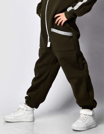 Cropped photo of legs A boy in a trendy warm sporty dark green jumpsuit poses for a studio portrait. schoolboy child standing over white background. Children's sportswear and fashion