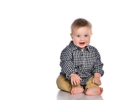 Funny little boy sits barefoot on the floor. The boy is wearing a plaid shirt and beige pants. The kid smiles happily on a white background with space for text. Stockfoto