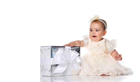 Little baby princess in a smart white dress sits in a white studio with a gift box with a ribbon.