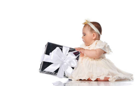 Beautiful baby girl child wearing festive dress and headband holding big gift box in wrap with bow. Kid receiving present. Studio full length portrait shot on white background. Birthday party concept Stockfoto