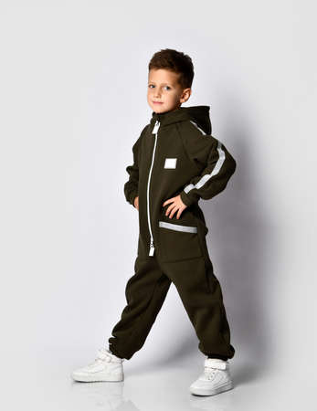Boy in trendy warm sporty dark green jumpsuit poses for a studio portrait. Beautiful schoolboy child standing over white background. Children's sportswear and fashion Stockfoto