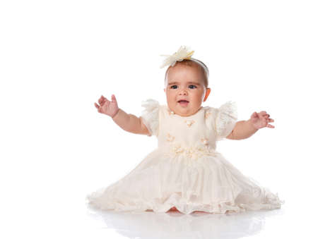 beautiful baby child in a festive dress and a headband, sitting on the floor and joyfully raised her hands. shot on a white background. Childrens fashion and beauty Stockfoto