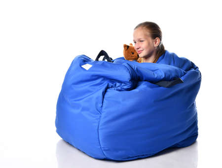child sits with a soft toy in a unique ball-shaped cocoon for development and sensory integration, rests Stockfoto