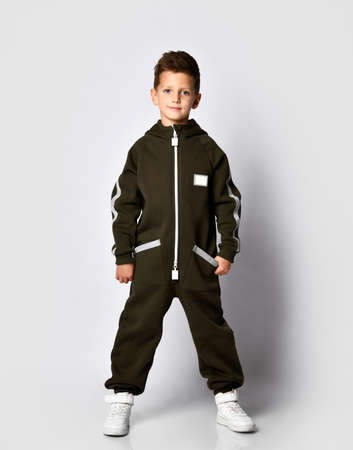 Full portrait of a modern boy in warm dark green jumpsuit and white giggles posing for the camera against a studio wall background. Sports fashion clothing and fashion for children