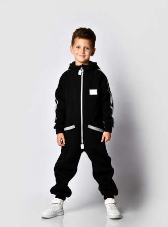 small brunette child in a black warm tracksuit, put on a hood on a gray background. Sports fashion. Whole length