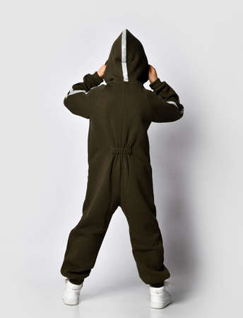 Full length portrait of modern boy wearing warm dark green jumpsuit with hood and white snickers posing for camera over studio wall background. Back side view. Sport trendy outfit and fashion for kids