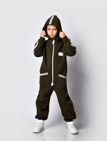 Full portrait of a modern boy in a warm dark green hooded jumpsuit and white sneakers posing for the camera against a studio wall background. Sports fashion clothing and fashion for children Stockfoto