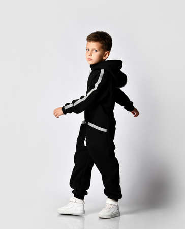 Handsome boy in black warm jumpsuit in full growth motion studio. The schoolboy turns around, showing the advantage and convenience of clothing. Kids fashion, casual wear, trendy clothing Stockfoto