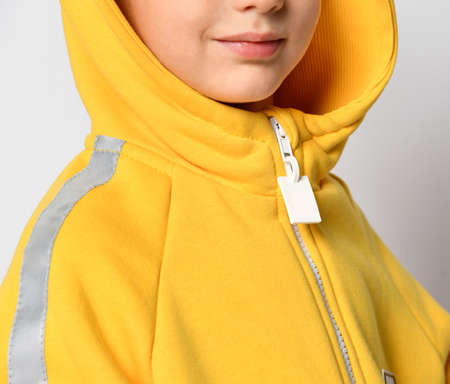 Closeup shot of warm yellow jumpsuit hood on boy model. Crop studio shot of trendy design sport wear for children. Detailed photo of costume for training and outdoor walk in autumn Stock Photo