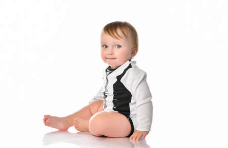 boy toddler portrait with blue eyes dressed in black and white bodysuit. The child is sitting barefoot and smiling happily on a white background with space for text.