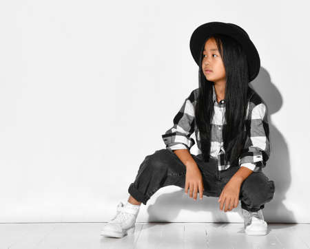 Stylish little asian girl with black hair sitting on a white background and looking to the side. Child looks at the free space for text or promotional products. Banner concept.