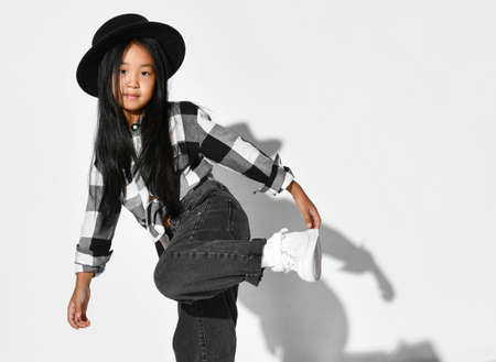 Portrait of an Asian girl with black hair who dances and has fun on a white background. The child wears a black hat, plaid shirt, jeans and looks into the camera. Children's fashion and style. Stockfoto