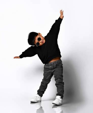 Portrait of a cute little boy in stylish clothes and sunglasses, arms outstretched and having fun at the white studio wall. Children's fashion concept.