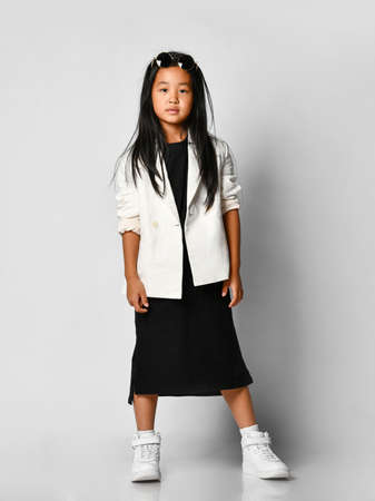 Profile of self-confident asian girl in black long t-shirt dress and white blazer looking at camera