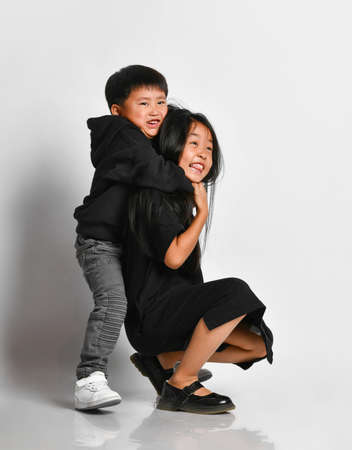 Little boy hugging his older sister from behind and smiling looking at the camera. Face of cute asian children on a white background with free space for text. Banner concept.
