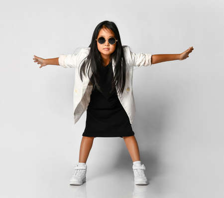 Little asian girl demonstrates stylish autumn children's clothes laughing at the camera with arms outstretched. Model is dressed in a black dress, white jacket and fashionable sunglasses.