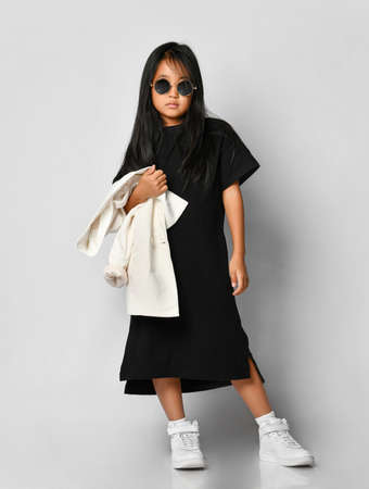 Full portrait of a confident asian korean girl in black long t-shirt dress, white blazer, and sneakers facing the camera