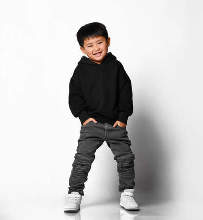 Cute and fashionable little asian preschool boy smiling with hands in jeans pockets on gray background