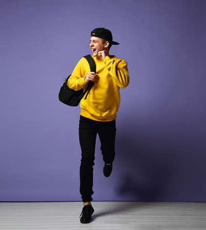 Joyful young man student with a backpack runs isolated in studio on a purple background. Stockfoto