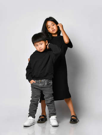 stylish brother and sister asian children posing in front of the camera in the studio on a white background. Cool boy in black hoodie and jeans with older sister in black dress having fun.
