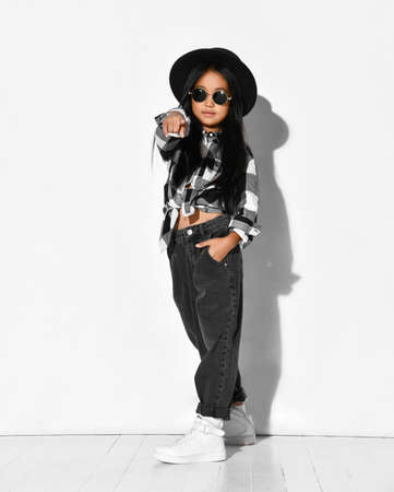 Stylish little Asian girl in a black hat, round glasses, a plaid shirt and jeans points her finger at a free space for text. Girl posing in studio on a white background. Banner concept.