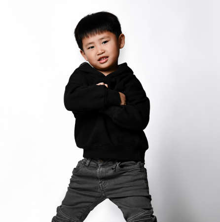 Cool Korean little boy in a stylish black sweatshirt with a hood and jeans posing in the studio on a white background and. New collection of comfortable children's clothing. Stockfoto