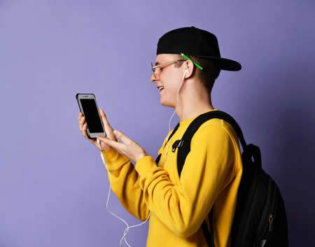 Portrait of a young student in a yellow sweater listening to music with headphones and holding a mobile phone, communicates with someone via video link. isolated on purple background Stockfoto