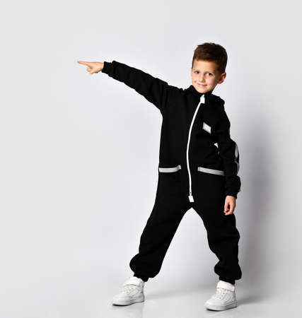 boy in a warm sports jumpsuit points with his hand to the side to the free space for your advertising, autumn fashion for children