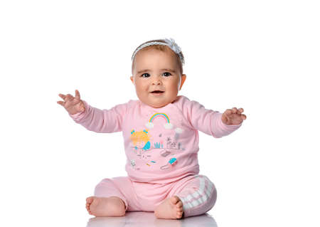 Happy laughing little sly infant girl in pink sportswear baby girl sitting on the floor looking at the camera. Happy infancy and childhood concept Stockfoto